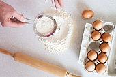 Man sow flour for dough