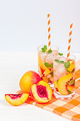 Peach lemonade with ice and mint leaves. Homemade lemonade of ripe nectarine with white and orange ripe. Two glasses of peach tea. Refreshing summer drink on a white wooden background.
