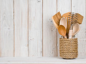 Wooden kitchen cooking utensils in handmade storage pot on shelf