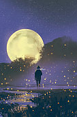 man standing in swamp with fireflies and full moon on background