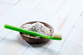 green toothbrush and ecological baking soda salt in wooden cup