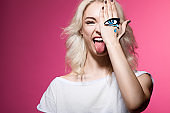 funny hipster girl with a tearful eye painted on your arm posing for the camera