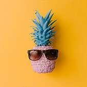 Pink pineapple with sunglasses on bright yellow background. Minimal style