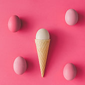 Ice cream cone with egg on pink background. Minimal Easter concept. Flat lay.