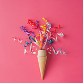 Ice cream cone with egg and party streamers on pink background. Minimal food concept. Flat lay.