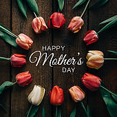 Creative arrangement of tulips on black background with happy Mothers day text. Flat lay.