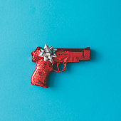 Gun wrapped in red paper with bow on blue background.