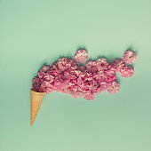 Ice cream cone with pink flowers and leaves. Summer minimal concept. Flat lay.
