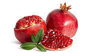 one whole and part of a pomegranate and leaves isolated on white background
