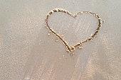 Heart drawn on a sand of beach