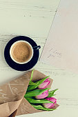 Cup of coffee with bouquet of pink tulips and notes I LOVE YOU