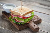 Close-up big sandwich with ham, cheese, tomatoes, salad and white sauce on toasted bread on a rustic wooden table