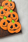 Homemade ginger cookies in the shape of pumpkins for Halloween. On the lighter concrete background. Top view