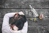 Drunk  girl sleeping at the old wooden table after the party. Bottle of vodka and pickles, shots and beer mug. Female alcoholism. Hangover. Alcohol dependence. Bad habit.