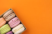 multicolored macaroons in a box on an orange background