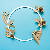 round frame with craft paper flowers on the blue background. Flat lay. Nature concept