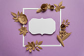 square frame with craft paper flowers on the violet background. Flat lay. Nature concept