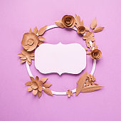 round frame with craft paper flowers on the violet background. Flat lay. Nature concept