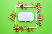 Vintage square frame with craft paper flowers on the green background. Flat lay. Nature concept