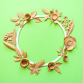 round frame with craft paper flowers on the green background. Flat lay. Nature concept