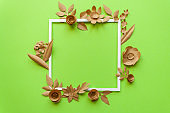 square frame with craft paper flowers on the green background. Flat lay. Nature concept