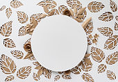 round frame with craft paper flowers on the background of leaves