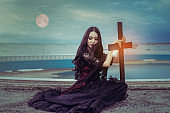 Witch or vampire beautiful woman sitting and holding cross the ghost with  screaming darkness and nightmare, horror of scary fear on hell in halloween festival, and blood moon refurbished by NASA