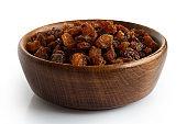 Dry raisins in dark wooden bowl isolated on white.