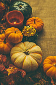 Fall season decorations - ripe pumpkins, maple leaves and candle