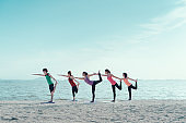 Young group yoga exercise practice  with pose on the beach relax vacation in summer