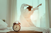 Closeup alarm clock, Young asian woman wake up in the morning and sitting on bed at mirror door side relaxing in holiday with sunlight, Vintage