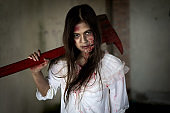 Zombie woman or ghost holding axe sitting with blood in house of ruin nightmare, horror of scary fear on hell is monster devil in halloween festival.