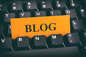 Yellow paper note on black keyboard with writing Blog