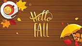 Hello Fall lettering on wooden background.