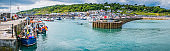 Fishing boats tourists on harbour wall Lyme Regis panorama Dorset