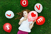 Cute little girl in a white T-shirt, hold a red balloon