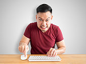Angry and furious man works with computer.