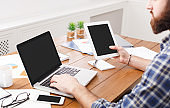 Young casual businessman working with laptop and tablet in office, close up