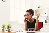 Business talk, furious woman talking on phone at office