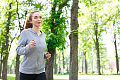 Young woman jogging in green park, copy space