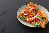 Sliced pizza with prosciutto and rocket salad