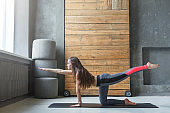 Young woman in yoga class doing stretching exercise