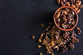 Nuts and raisins at black background. Healthy source of fat for vegans and vegetarians