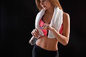 Beautiful young sport woman with towel and water