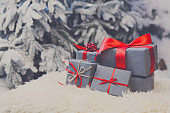 Christmas gifts on blurred fir tree background, holiday concept