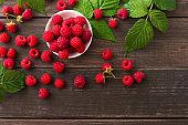 Red fresh raspberries on brown rustic wood background