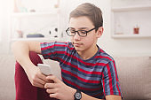 Teenager with mobile phone in living room at home