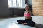 Young woman in yoga class, relax half lotus pose