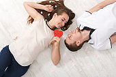 Young couple in love lying on floor, top view