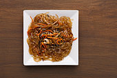 Asian food in a bowl at rustic wooden background, top view